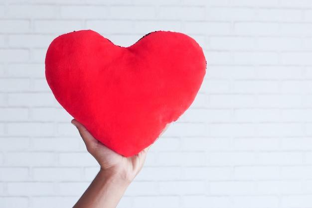 Hand met rood hartsymbool op witte achtergrond.