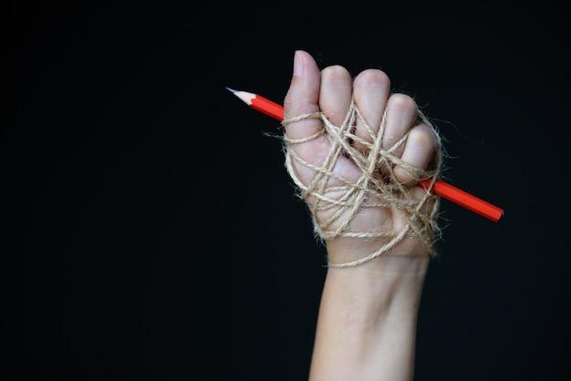 Hand met rood potlood dat met kabel, het concept van de de vrijheidsdag van de wereldpers wordt gebonden.