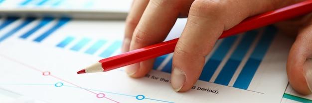 Hand met rood potlood ligt op vergelijkende grafiek. bouw individuele grafieken of bekijk leadoverzichtsgegevens. graaf diep in cijfers en werk er handmatig mee. vergelijkende kenmerken verschillende bedrijven