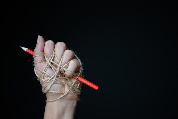 Hand met rood potlood vastgebonden met touw, beeltenis van het idee van de vrijheid van de pers