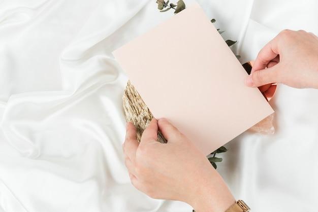 Hand met roze lege uitnodigingskaart