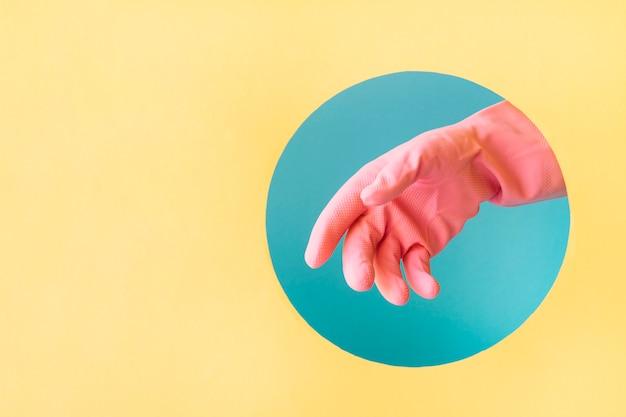 Hand met roze rubberen handschoenen