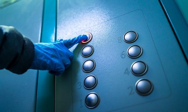 Hand met rubberen blauwe handschoen die op de liftknoppen drukt