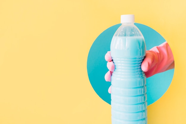 Hand met rubberen handschoenen met plastic fles