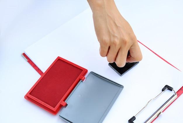 Hand met rubberen stamper met rode stempelkussen (doos) op wit papier.