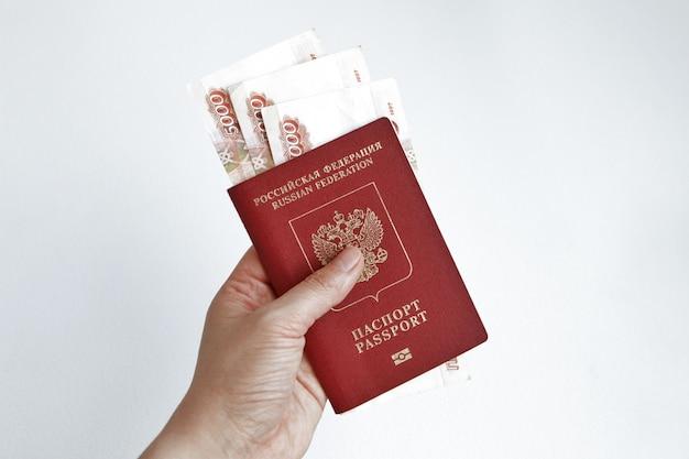 Hand met russisch paspoort met bankbiljetten van 5000 roebel