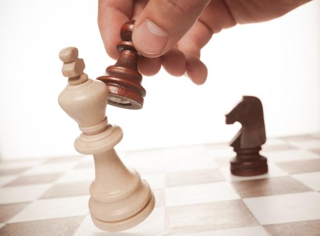 Hand met schaakpion die de koning duwt