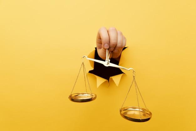 Hand met schalen van geel gescheurd papier