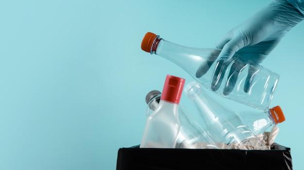 Hand met schoonmaakhandschoen een gebruikte plastic fles in de prullenbak laten vallen