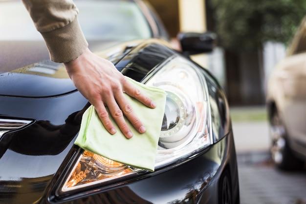 Hand met servet schoonmaken koplamp van donkere auto