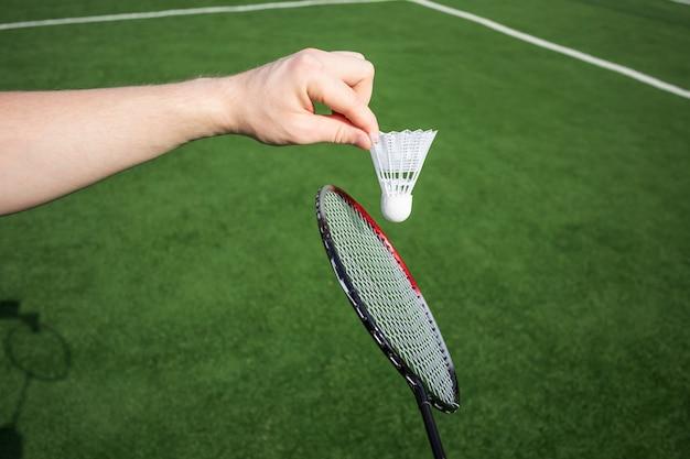 Hand met shuttle op gras, een racket dichtbij.