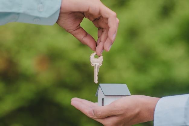 Hand met sleutel en huis, zakelijke verkoper financiën verhuur
