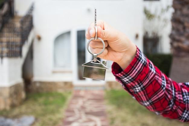 Hand met sleutel met een sleutelhanger in de vorm van het huis