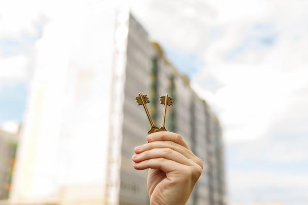 Hand met sleutels tot nieuw huis. aankoop, huur, koop, verkoop, lening of vastgoedlening, hypotheek.