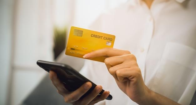 Hand met smartphone en met behulp van applicatie die online winkelt met betaling per creditcard online.