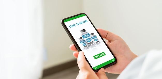 Hand met smartphone en webpagina coronavaccin online weergeven met knop voor meer informatie.