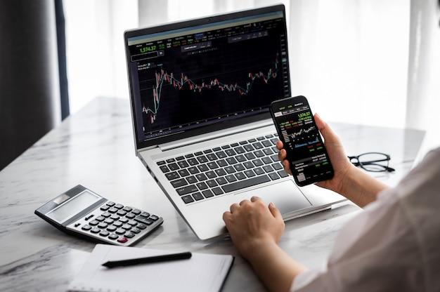 Hand met smartphone met beursgegevens en met behulp van laptop display grafiek en grafiek voor analyse. â online beleggingsconcept