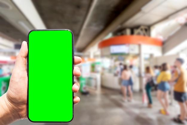 Hand met smartphone met groen scherm