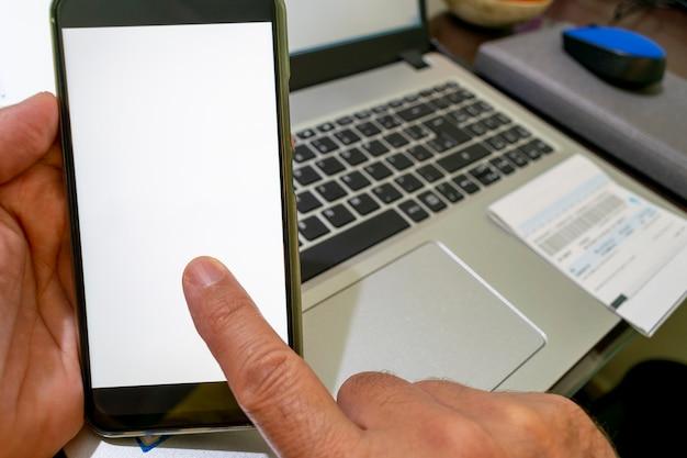 Hand met smartphone met vinger op wit scherm en computer op de achtergrond.