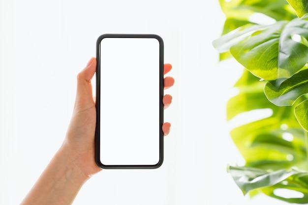 Hand met smartphone mockup van leeg scherm op tafel.