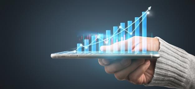 Hand met smartphoneapparaat en scherm aan te raken. beursmarkt concept. handelaar die met de kaars van de grafiekenanalyse kijkt
