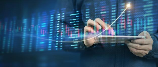 Hand met smartphoneapparaat en scherm aan te raken. beursmarkt concept. zakenman handelaar kijken met grafieken analyse kaars