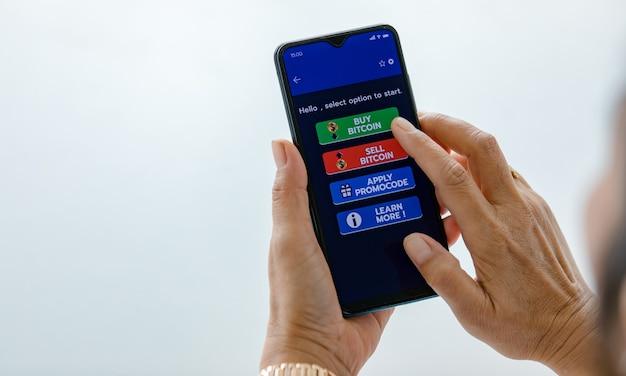 Hand met smartphones en gebruik vingeraanraking op het scherm en selecteren op knoppen van koop- en verkoopapplicatie voor bitcoin of cryptocurrency digitale geldhandel met kopieerruimte