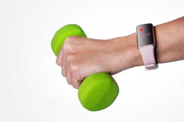 Hand met smartwach tijdens het sporten op lichtgrijze achtergrond.