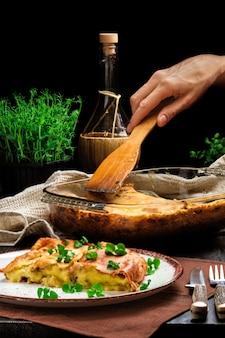 Hand met spatel portie aardappelpuree gebakken in oven
