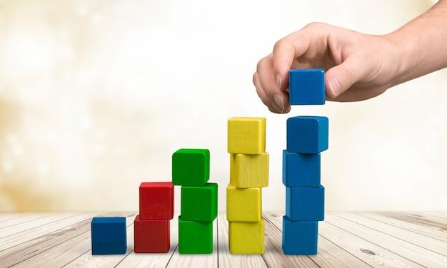 Hand met speelgoed houten blokken stapel, torens van lege veelkleurige doos kubussen op witte achtergrond