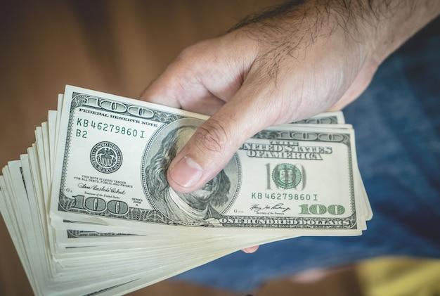 Hand met stack van dollar bankbiljetten bovenaanzicht