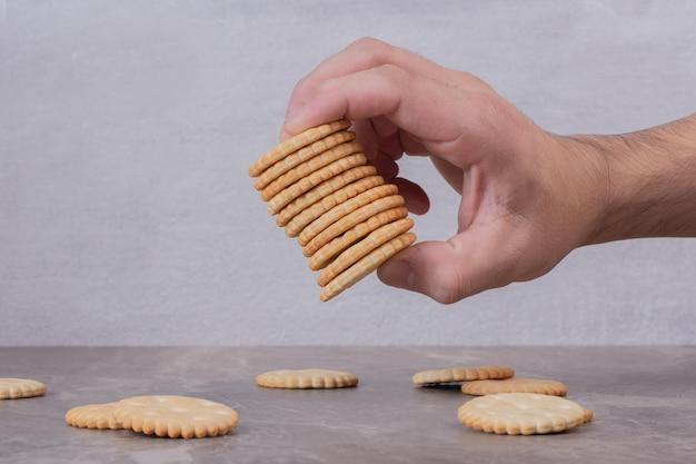 Hand met stapel koekjes op marmeren tafel.