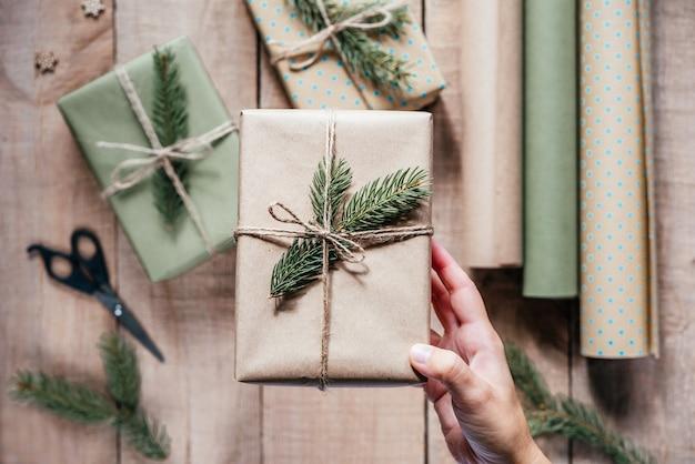 Hand met stijlvolle, milieuvriendelijke geschenkdoos verpakt in ambachtelijk papier en versierd met dennenboomtak