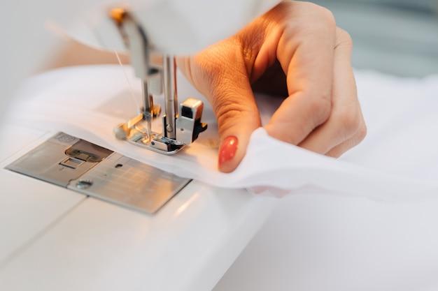 Hand met stof en naaimachine.