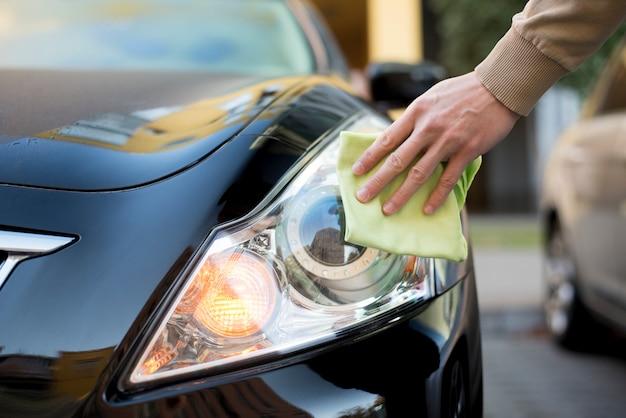 Hand met stofdoek schoonmakende koplamp van donkere auto