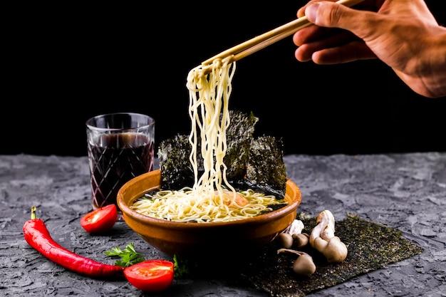 Hand met stokjes en noedels soep