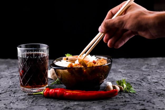 Hand met stokjes en rijstkom