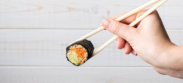 Hand met stokjes en sushi roll