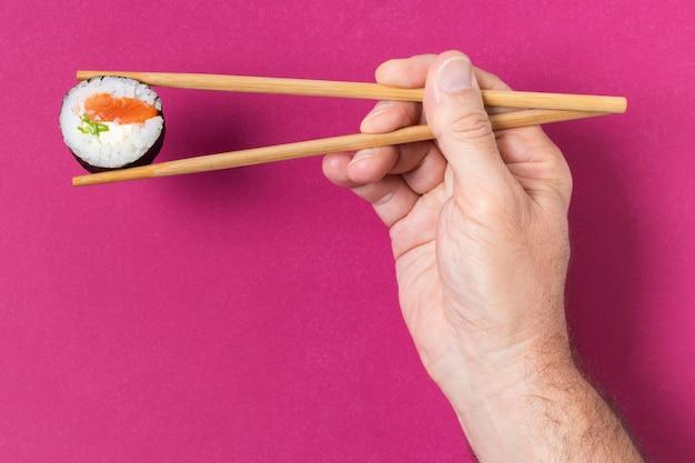 Hand met stokjes en sushi