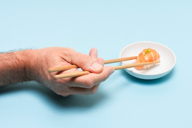 Hand met stokjes eten sushi