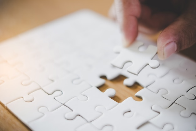 Hand met stuk van de lege puzzel met papier frame achtergrond.