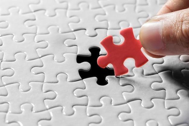 Hand met stuk van lege puzzel