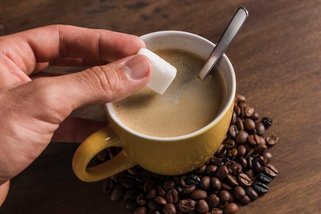 Hand met suiker in de buurt van beker met koffie