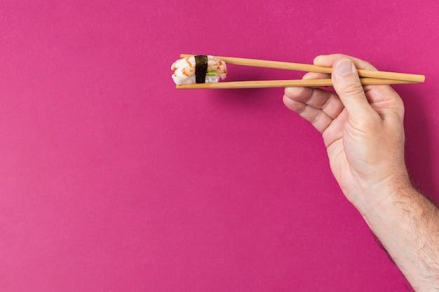 Hand met sushi op stokjes