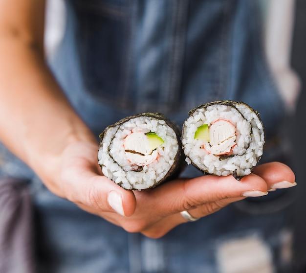 Hand met sushi rolt