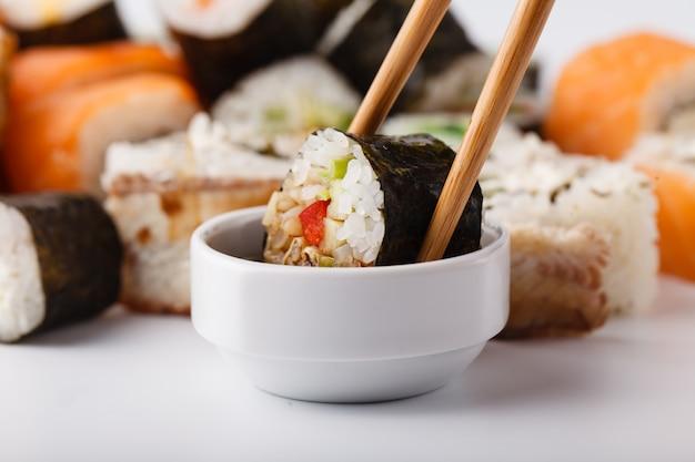 Hand met sushi zalm roll in stokjes met kopie ruimte voor ontwerpwerk