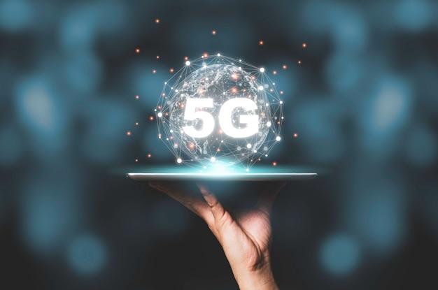 Hand met tablet met 5g en virtuele wereldwijde verbindingslijn. communicatie technologie transformatie concept.