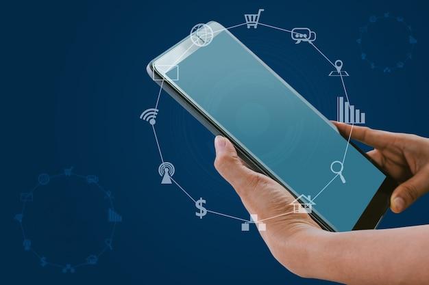 Hand met tablet met wazige sociale media en technologie pictogrammen op blauwe kleur achtergrond.