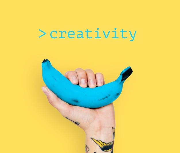 Hand met tatoegering die blauwe banaan met gele achtergrond opheft