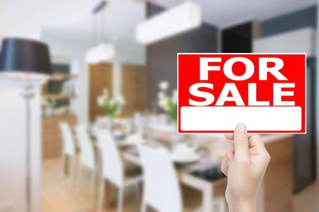 Hand met te koop huis bord met huis interieur achtergrond
